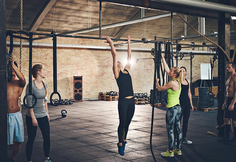 Adultos haciendo flexiones en el bar en el gimnasio