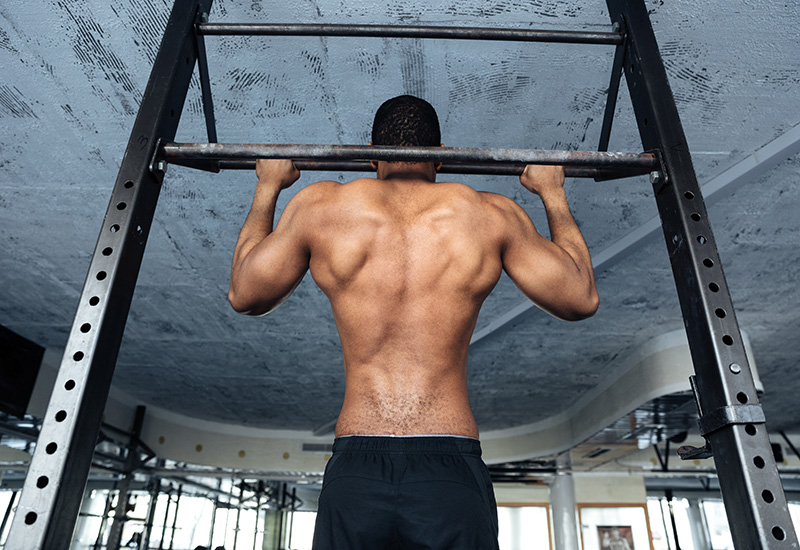Atleta fuerte haciendo pull-up en barra horizontal