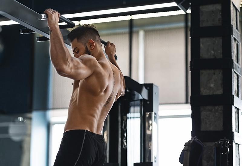 Atleta muscular tirando hacia arriba en barra horizontal en el gimnasio