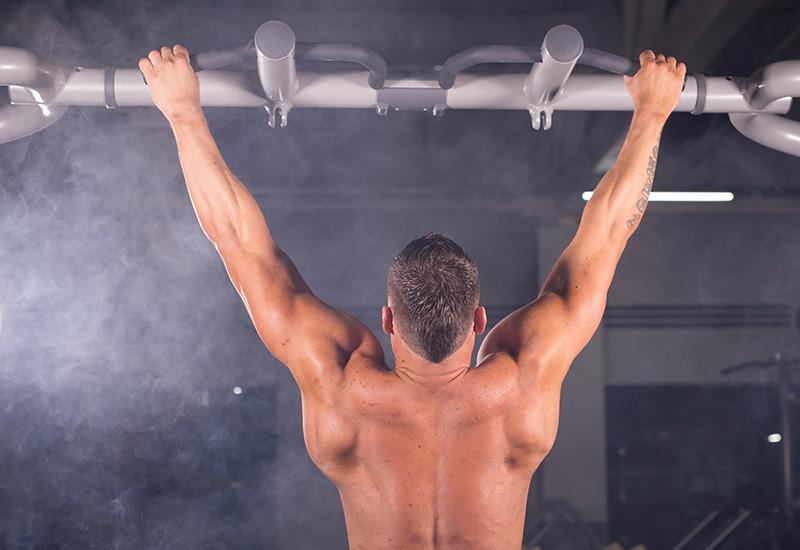 Deportista muscular fitness modelo masculino tirando hacia arriba en barra horizontal en un gimnasio.