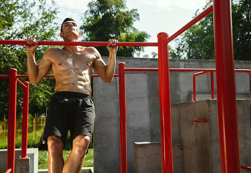 Hombre musculoso joven mientras hace su entrenamiento fuera en el patio de recreo