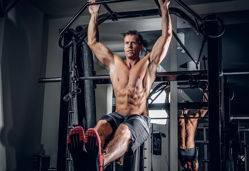 Un hombre haciendo ejercicios abdominales en la barra de tracción.