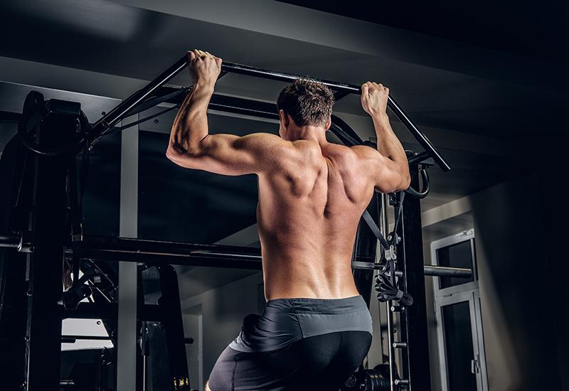 Un hombre haciendo flexiones en la barra horizontal.